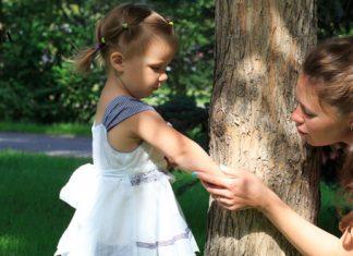 Мама проверяет руку ребенка на укус насекомого