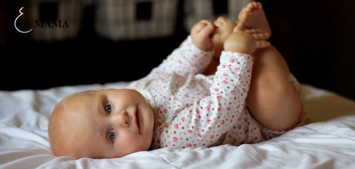 Малыш лежит на спине и держит себя за ножки