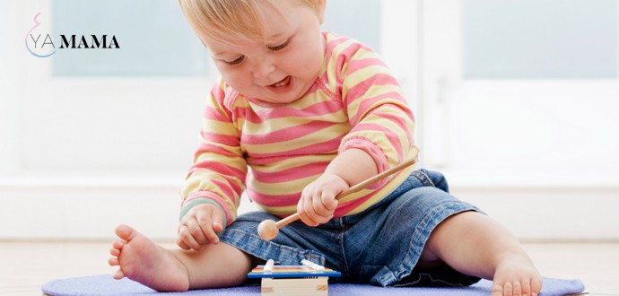 Малыш играет с игрушкой, сидя на полу