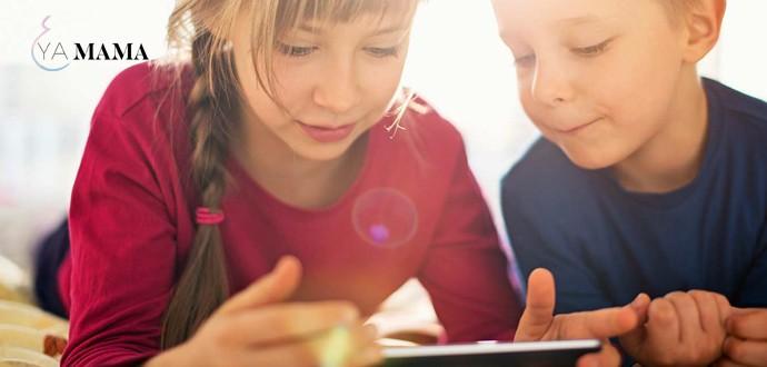 Мальчик с девочкой читают с планшета, лежа на животе