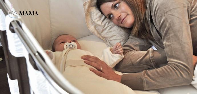 Мама проверят, как малыш спит в приставной детской кроватке