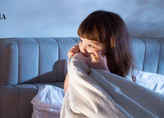 Напуганная девочка сидит в кровати, прячась под одеялом