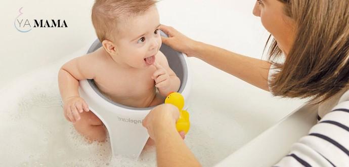 Малыш сидит в ванне в детском сиденье