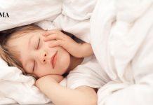 Ребенок спит, укрывшись одеялом с головой
