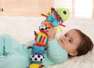 Малыш держит в руках мягкую игрушку, лежа на полу