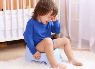 Малыш плачет, сидя на горшке