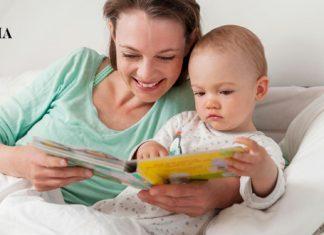 Мама с малышом читают книжечку в постели