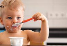 Малыш кушает йогурт ложкой