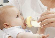 Женщина кормит из бутылочки грудничка