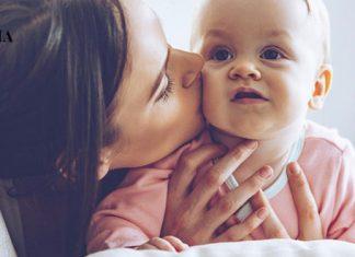 Мама целует младенца в щеку