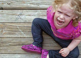 Девочка плачет, сидя на деревянной поверхности