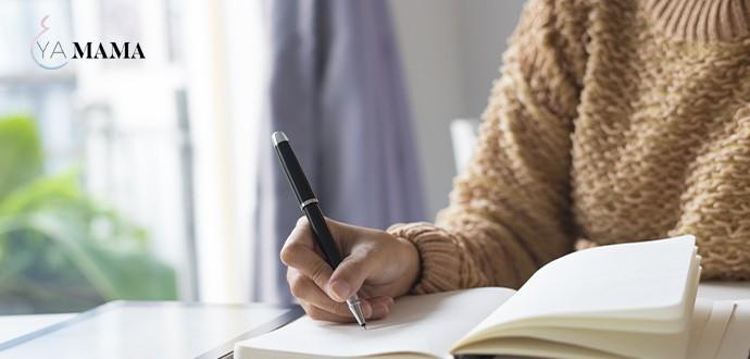 молодая мама пишет планы на день в блокнот