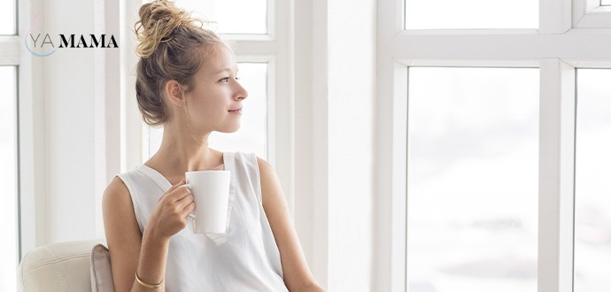 молодая мама пьет кофе