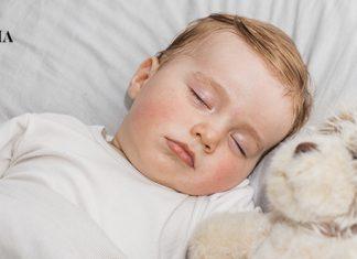 малыш спит со своей игрушкой в кроватке