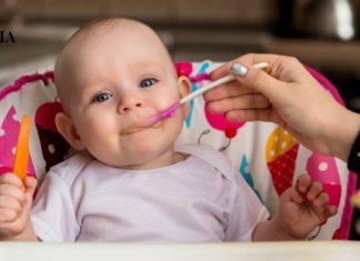 мама кормит маленькую дочку из ложечки