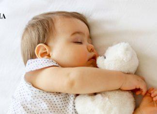 маленькая девочка спит со своей игрушкой