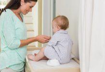 Мама разговаривает с ребенком на пеленальном столике