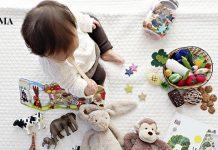 маленький мальчик сидит на полу со своими игрушками