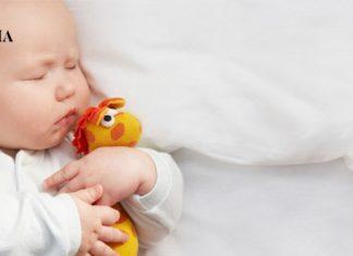 ребенок лежит в кроватке со своей игрушкой