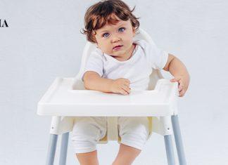 малыш сидит в своем стульчике для кормления