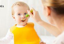 молодая мама кормит свою дочь из ложечки