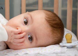 малыш лежит в кроватке и сосет палец