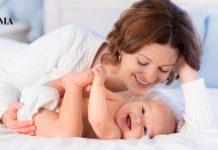 молодая мама лежит с ребенком на кровати