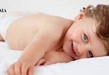 маленький мальчик лежит в кроватке