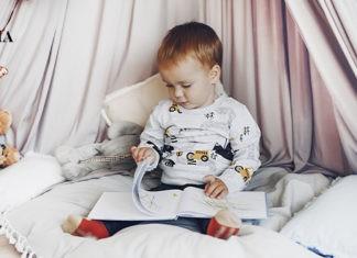 малыш сидит с книгой