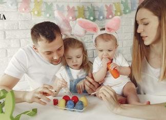 родители с детьми расскрашивают яйца к Пасхе