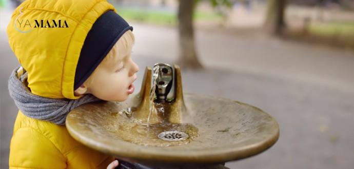 маленький мальчик пьет проточную воду